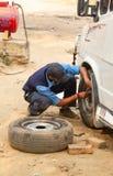 A man fixes a wheel at the car stock photos