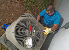 Man fixing air conditioner. Male Hispanic air conditioning technician fixing central air Royalty Free Stock Photos