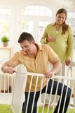 Man fixing baby bed Stock Photography
