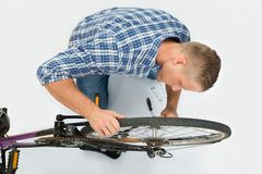 Man Fixing Bicycle Wheel Stock Images