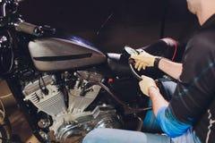 Man fixing bike. Confident young man repairing motorcycle near his garage. barometer. Man fixing bike. Confident young man repairing motorcycle near his garage royalty free stock photo