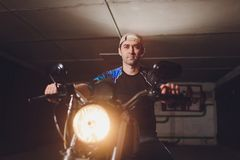 Man fixing bike. Confident young man repairing motorcycle near his garage. Man fixing bike. Confident young man repairing motorcycle near his garage royalty free stock photos