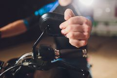 Man fixing bike. Confident young man repairing motorcycle near his garage. rearview mirror adjustment. Man fixing bike. Confident young man repairing motorcycle royalty free stock images
