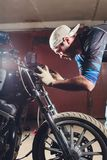 Man fixing bike. Confident young man repairing motorcycle near his garage. replacement lamp in the headlamp. Man fixing bike. Confident young man repairing stock images