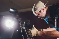 Man fixing bike. Confident young man repairing motorcycle near his garage. replacement lamp in the headlamp. Man fixing bike. Confident young man repairing stock photography