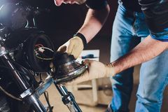 Man fixing bike. Confident young man repairing motorcycle near his garage. replacement lamp in the headlamp. Man fixing bike. Confident young man repairing royalty free stock photo