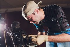 Man fixing bike. Confident young man repairing motorcycle near his garage. replacement lamp in the headlamp. Man fixing bike. Confident young man repairing royalty free stock photography
