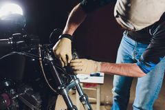 Man fixing bike. Confident young man repairing motorcycle near his garage. replacement lamp in the headlamp. Man fixing bike. Confident young man repairing stock photo