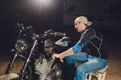 Man fixing bike. Confident young man repairing motorcycle near his garage. Man fixing bike. Confident young man repairing motorcycle near his garage stock photos