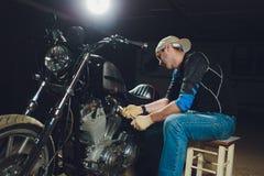 Man fixing bike. Confident young man repairing motorcycle near his garage. Man fixing bike. Confident young man repairing motorcycle near his garage royalty free stock images