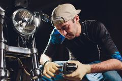 Man fixing bike. Confident young man repairing motorcycle near his garage. caliper, brake pad replacement. Man fixing bike. Confident young man repairing royalty free stock photos