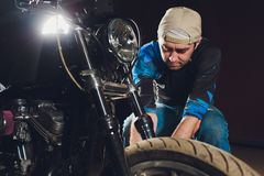 Man fixing bike. Confident young man repairing motorcycle near his garage. caliper, brake pad replacement. Man fixing bike. Confident young man repairing stock images