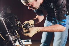 Man fixing bike. Confident young man repairing motorcycle near his garage. replacement lamp in the headlamp. Man fixing bike. Confident young man repairing royalty free stock photos