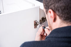 Man fixing a cabinet with a screwdriver Stock Images