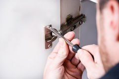 Man fixing a cabinet with a screwdriver Stock Photography