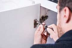 Man fixing a cabinet with a screwdriver Royalty Free Stock Images