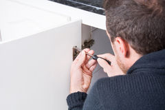 Man fixing a cabinet with a screwdriver Royalty Free Stock Photography