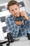 Man fixing camera lens on office table Stock Photography