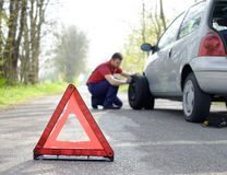 Man fixing a car problem after vehicle breakdown on the road Stock Photo