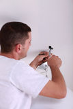 Man fixing ceiling light Stock Photos