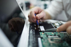 Man Fixing Components in Disassembled Laptop Royalty Free Stock Photography