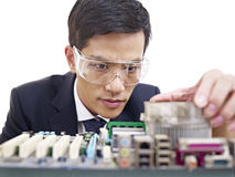 Man fixing computer. Young asian man fixing computer with protective eyewear Stock Images