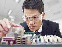 Man fixing computer. Young asian man fixing computer with protective eyewear Stock Photo