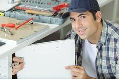 Man fixing cupboard door. Man fixing the cupboard door stock photo