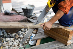 Man fixing decking by sawing a wood with hand wood saw royalty free stock photo