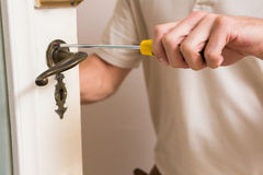 Man fixing the door handle with screwdriver. In a new house Royalty Free Stock Photography
