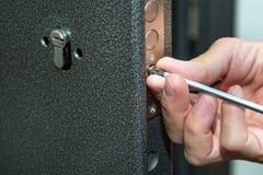 Man fixing the door with screwdriver. Door lock repair. Installation of a lock in the door stock image