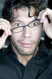 Man fixing his glasses. Confused young man fixing his glasses Royalty Free Stock Image