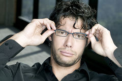 Man fixing his glasses. Funny looking young man fixing his glasses Stock Image