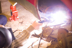 A man is fixing his rusty car with welding.  Royalty Free Stock Image