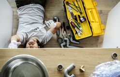 Man fixing the kitchen sink stock photo