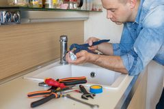 Man fixing leaking tap in kitchen stock photos