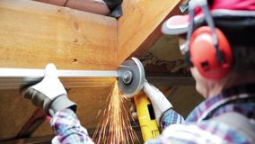 Man fixing metal frame using angle grinder on attic ceiling covered with rock wool. In natural light stock video footage