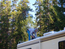 A man fixing a motor home at a national forest. Checking the air-conditioning equipment on an rv Royalty Free Stock Image