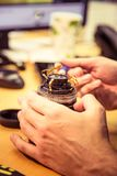 A man fixing photo camera lens on an office table. Indoors Royalty Free Stock Photography