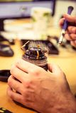 A man fixing photo camera lens on an office table. Indoors Stock Image