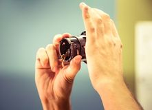 A man fixing photo camera lens on an office table. Indoors Stock Photo
