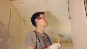 Man fixing plank with nails on wall. Side view of man in gloves and protective glasses attaching wooden plank on wall with hammer and nails stock video