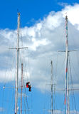 Man Fixing Sailboat Rigging. A man sits on one of the spars to repair the rigging on the main mast of a racing sailing ship. Vertical perspective taken in Royalty Free Stock Images