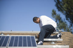 Man Fixing Solar Panel On Rooftop Stock Images