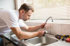 Man fixing tap with pliers. At home in the kitchen Stock Photography