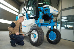 Man fixing tractor in agro-industrial hardware Royalty Free Stock Image