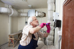Man fixing ventilation stack Royalty Free Stock Photography