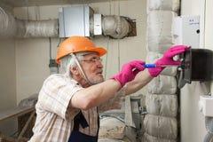 Man fixing ventilation stack Royalty Free Stock Photo