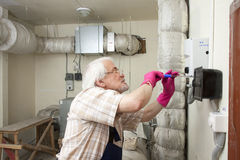 Man fixing ventilation stack Royalty Free Stock Images