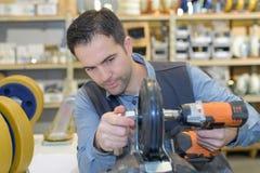 Man fixing wheel motorized vehicle. Man fixing small wheel of motorized vehicle Stock Image